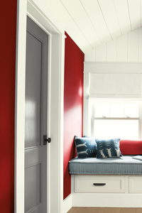 How to decorate your bedroom with red and crisp white for a modern look even nautical - this could be in the Hamptons! Grey door and window bench sitting. Benjamin Moore has revealed Caliente AF-290 as its highly anticipated Colour of the Year 2018. Unveiled alongside a corresponding palette consisting of 22 enlivening hues, this vibrant and charismatic shade of red is a bold yet soothing contemporary colour that oozes confidence. Wall colour - Caliente AF-290, Trim & Door colour - White Opulence OC-69