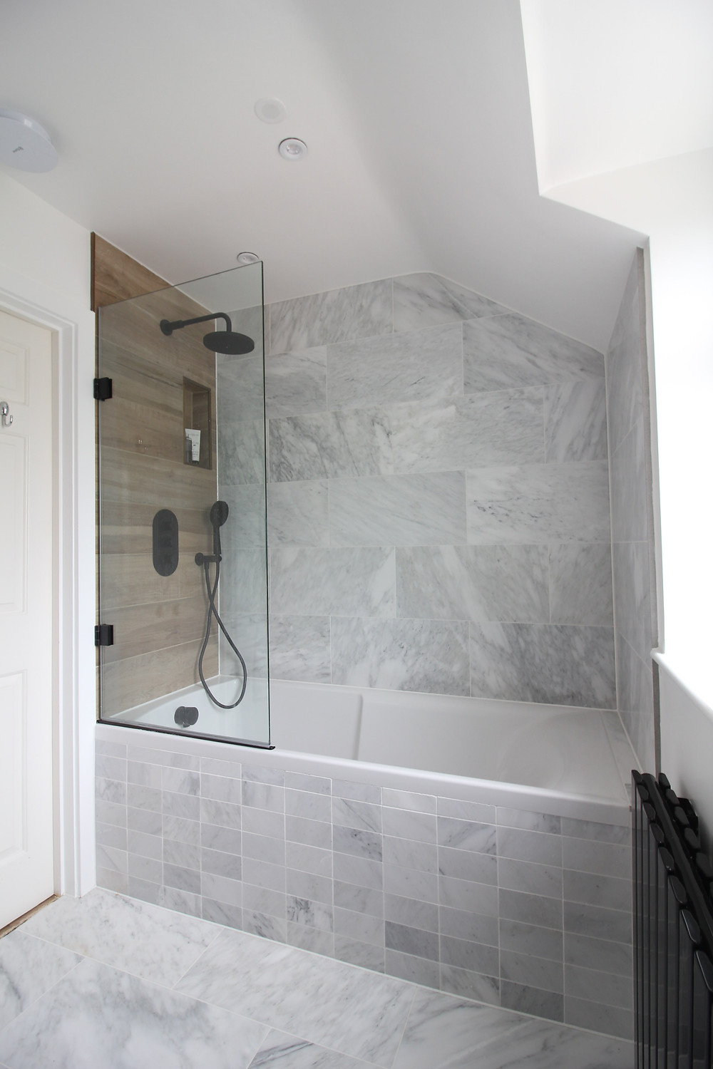 Alsace Honed Marble tiles Mandarin Stone, small bathroom design, renovation ideas, black taps and a black Milano slim Radiator, the Cadmium 18 bath screen The Shower Lab