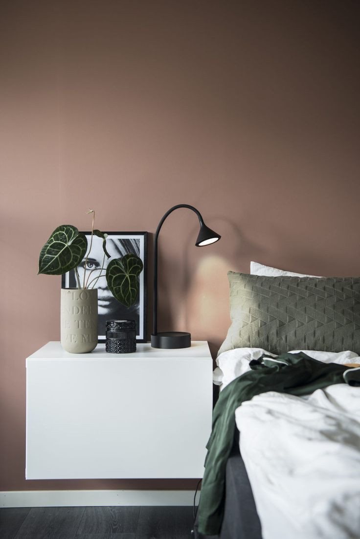 bedroom bedside table decor with black task lamp and terracotta wall
