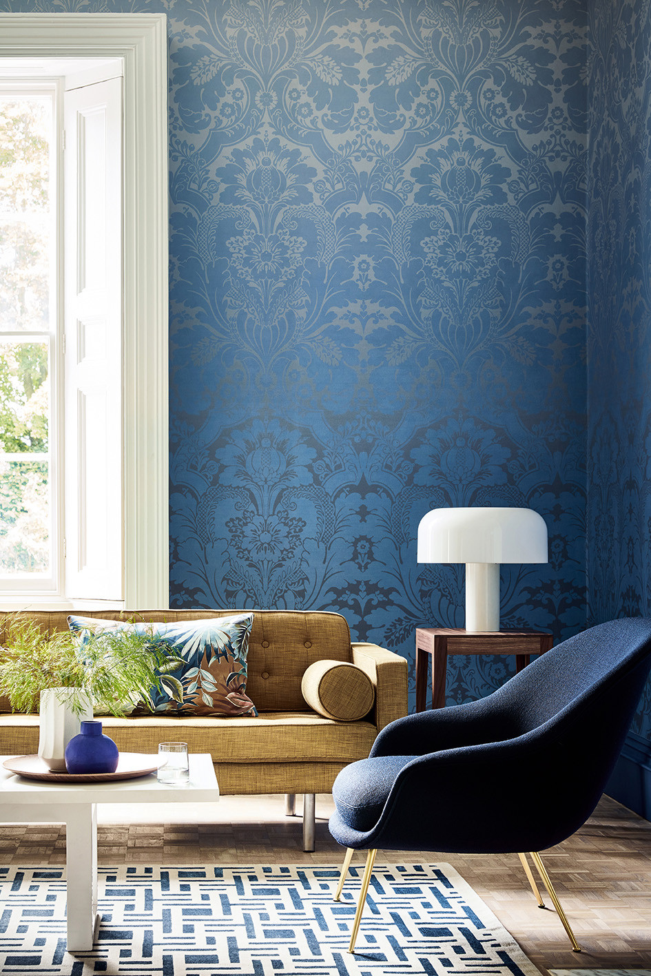 Little Greene LONDON WALLPAPERS V St James's Park - Suede Fade living room with blue wallpaper and white lamp, geometric rug