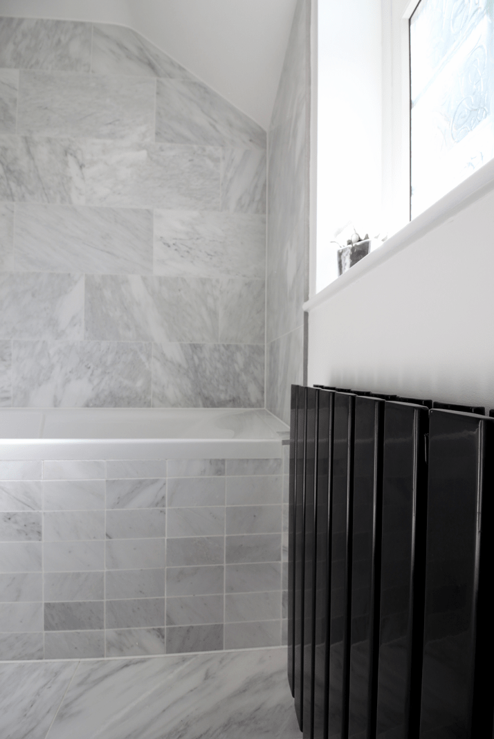 black Milano slim Radiator in a small designer bathroom with walls painted in Shirting by The Little Greene company and tiles from Mandarin Stone Alsace Honed Marble