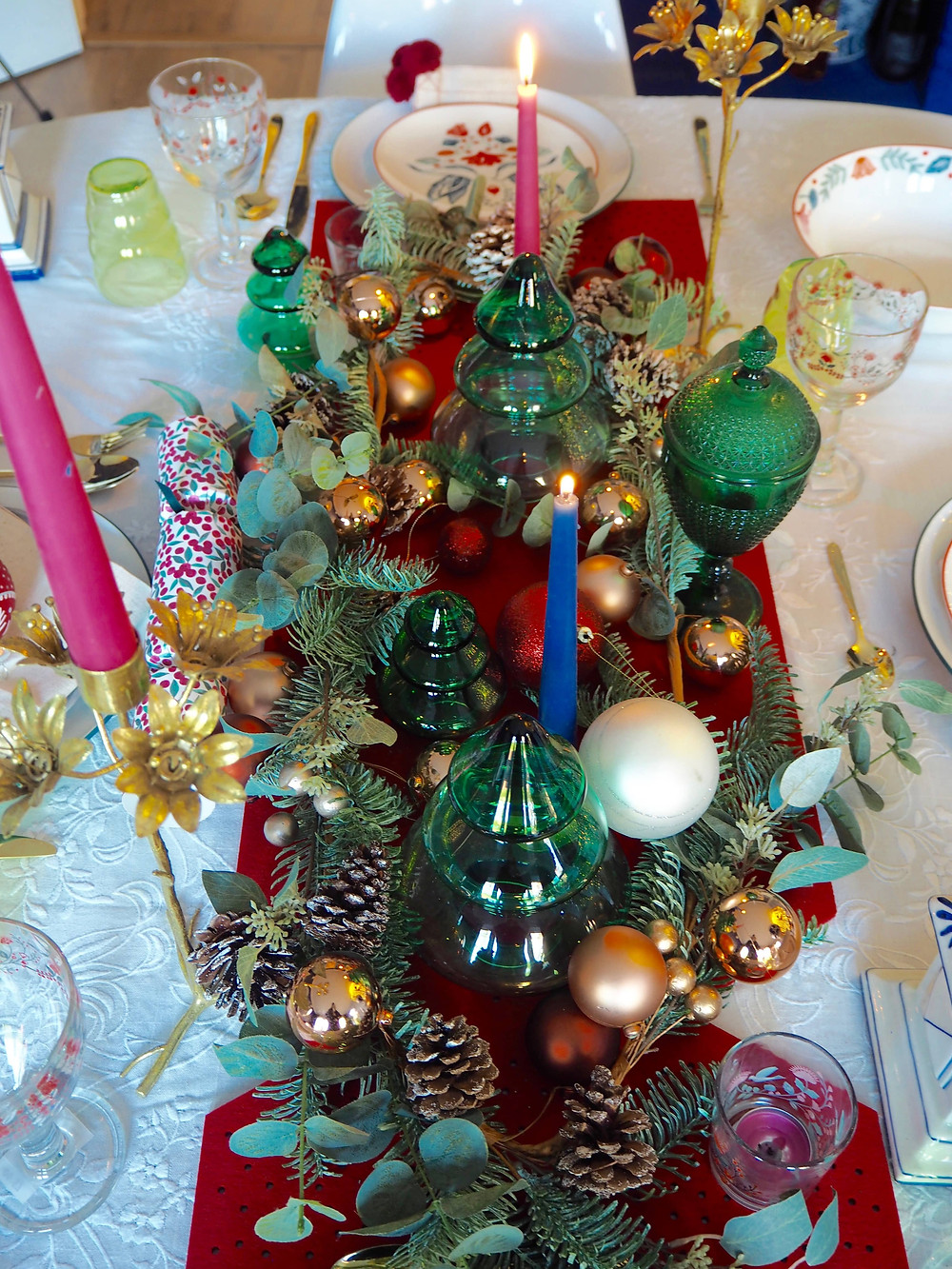How to set your Christmas table with John Lewis Christmas crackers in pink and green with blue background and fairy lights, felt cracker centrepiece from the Folklore collection. Gold cutlery table setting. How to make a centrepiece with baubles and ornaments