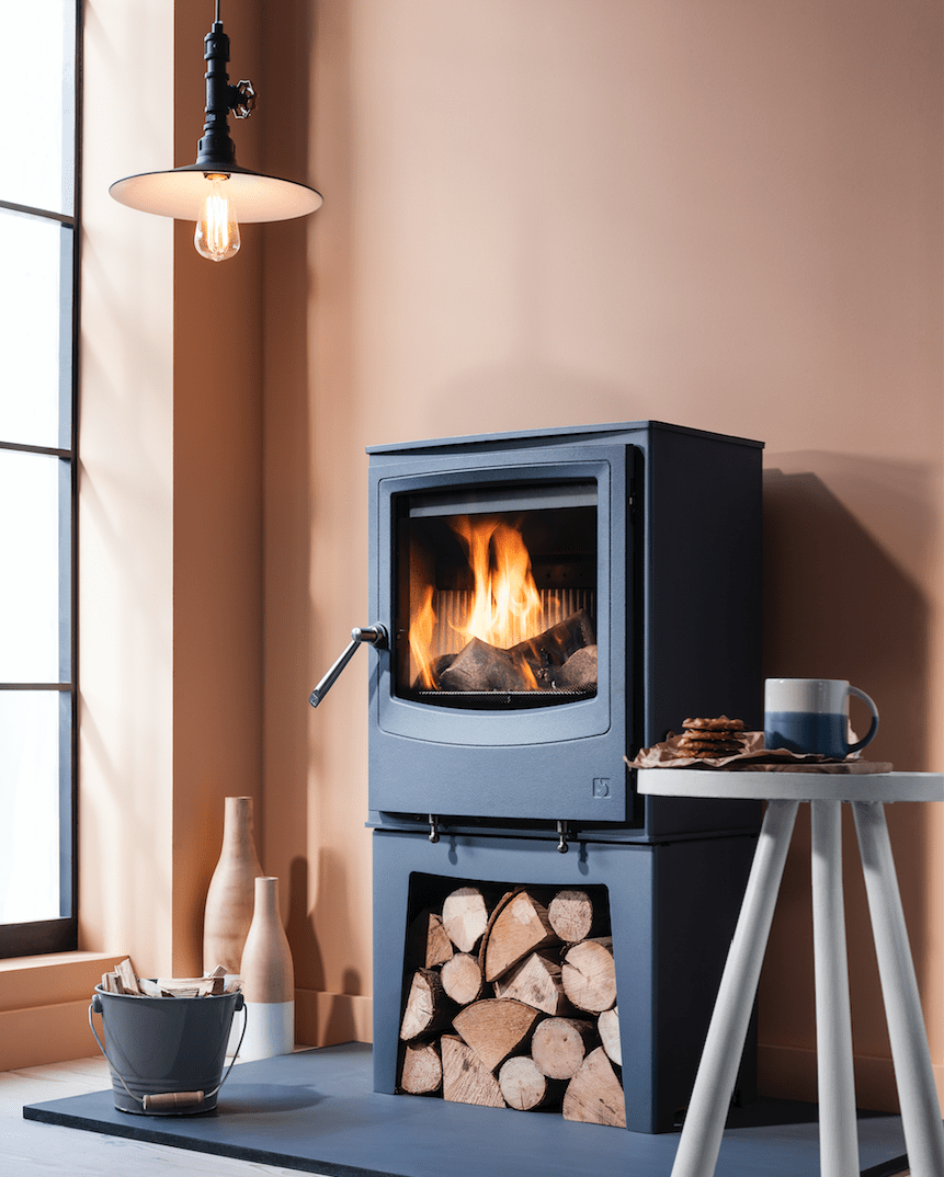 A tall farringdon wood burning stove with storage for wood underneath