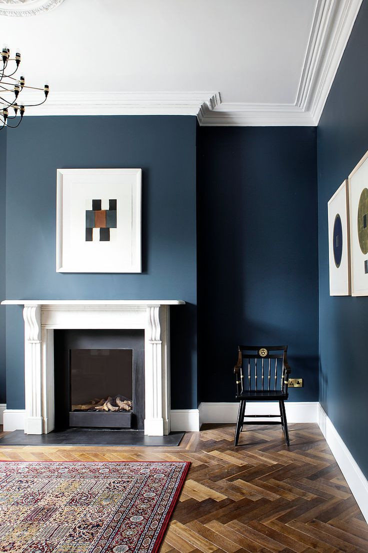 MID CENTURY STYLE LIVING ROOM painted in a deep blue colour with white skirt boards