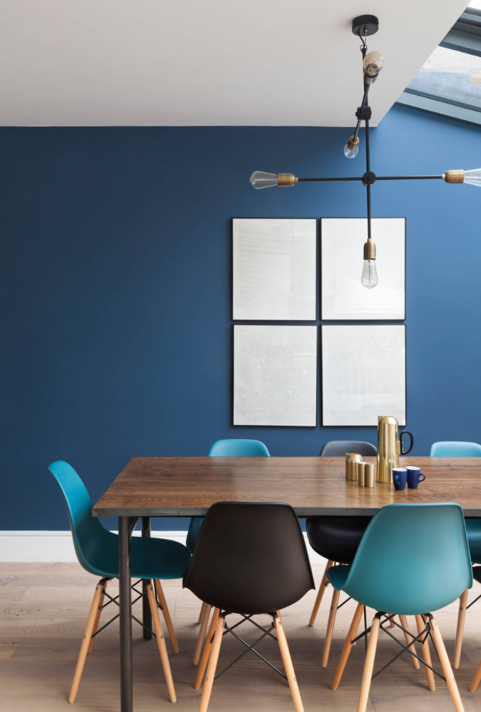 a dining table with Blue Eames chairs against a blue wall with a pendant light