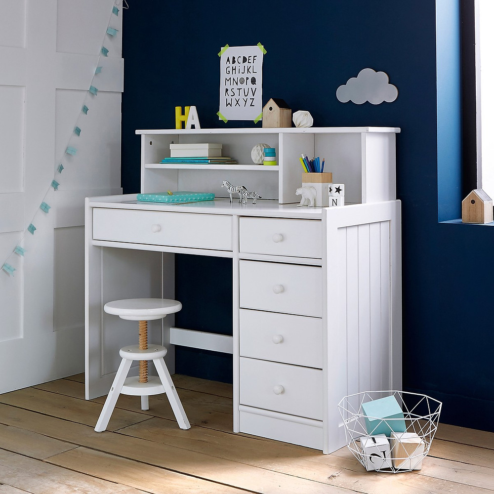 white stool with raised seat in front of white modular furniture with blue and teal accessories