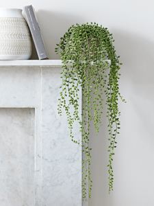String of Pearls pot on a fireplace
