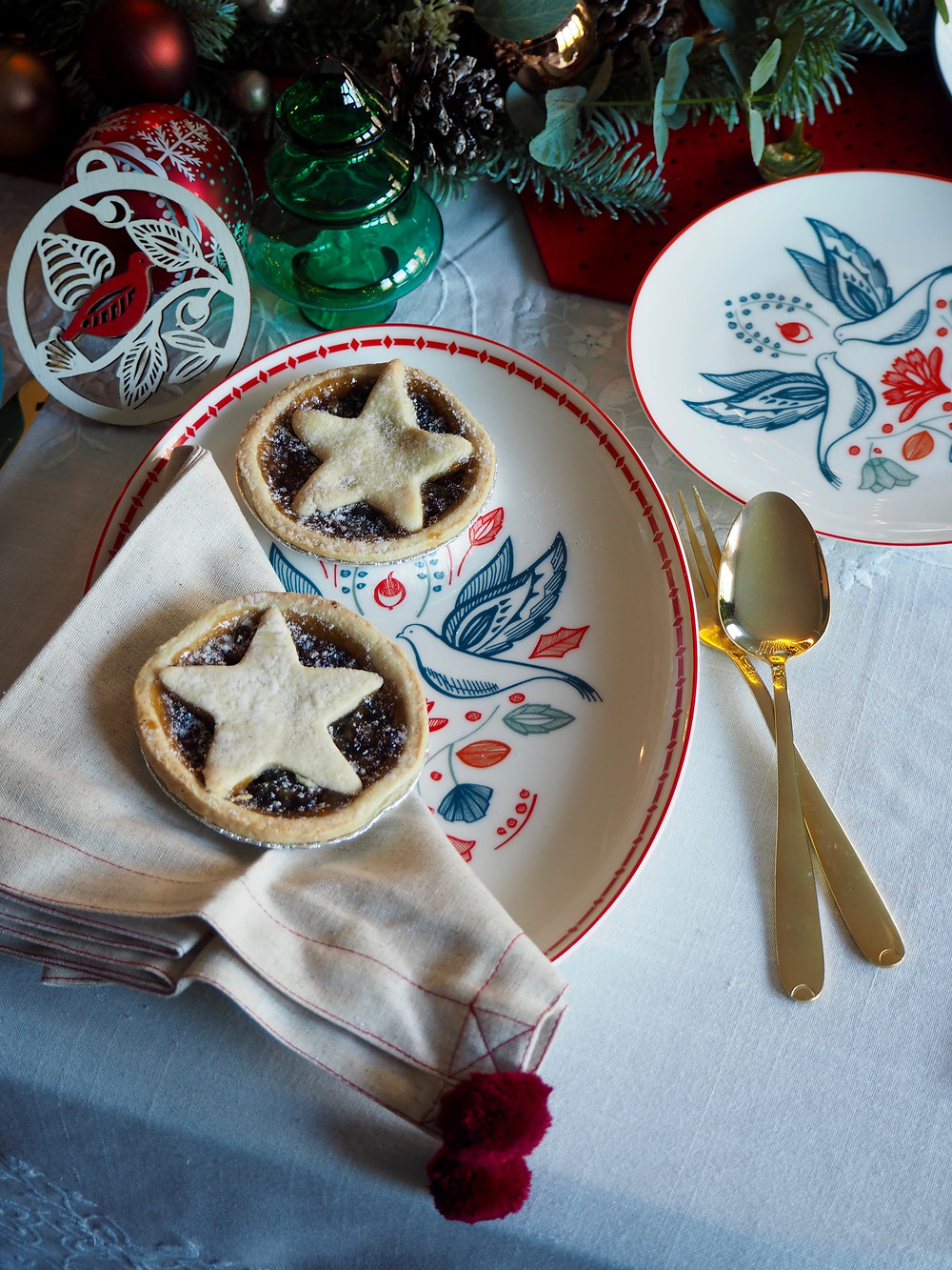 Mince pies on a white tablecloth. How to set your Christmas table with John Lewis Christmas crackers in pink and green with blue background and fairy lights, felt cracker centrepiece from the Folklore collection. Gold cutlery table setting. white vintage tablecloth