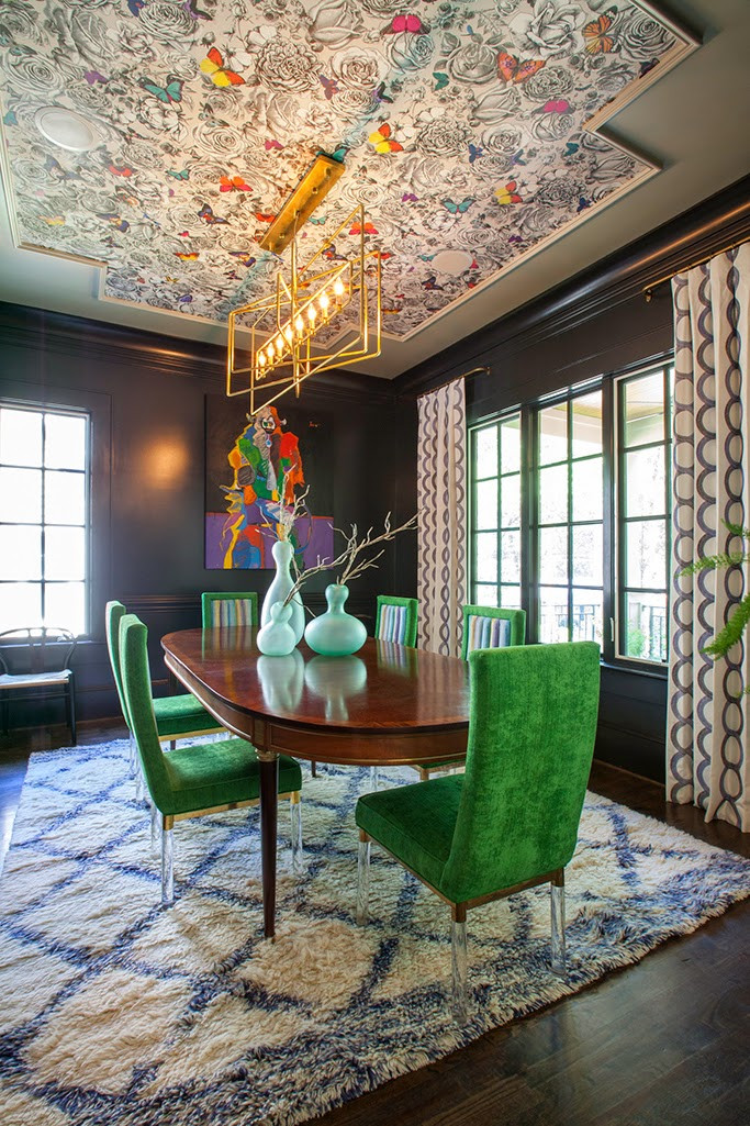 forest green chairs and black walls with wallpaper on the ceiling butterflies