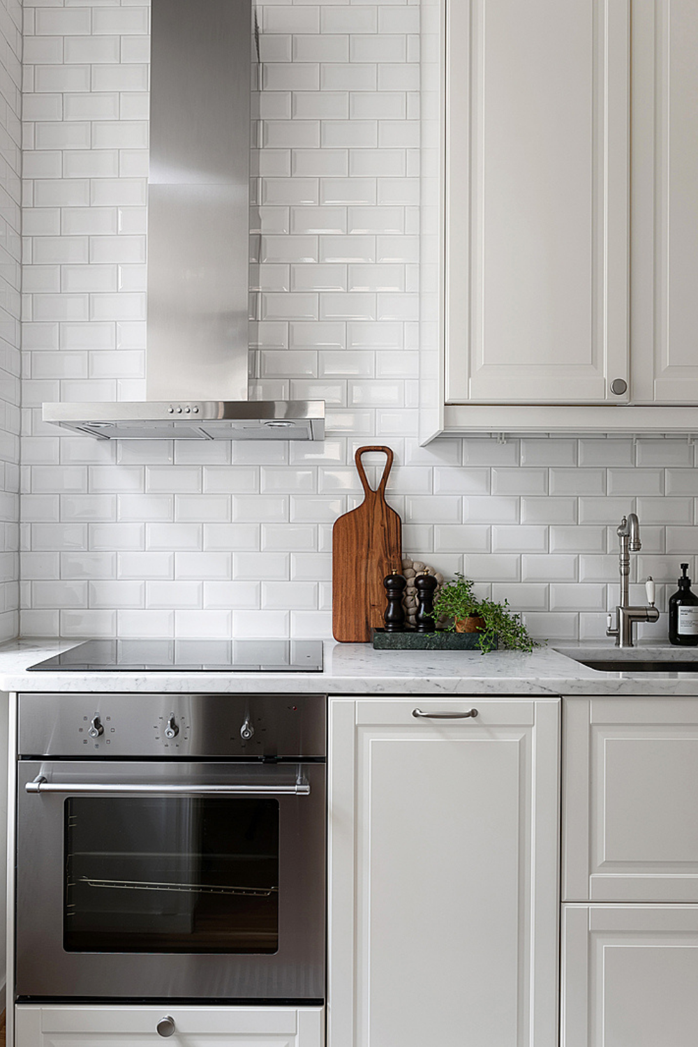 white kitchen with metro tiles and stainless steel appliances