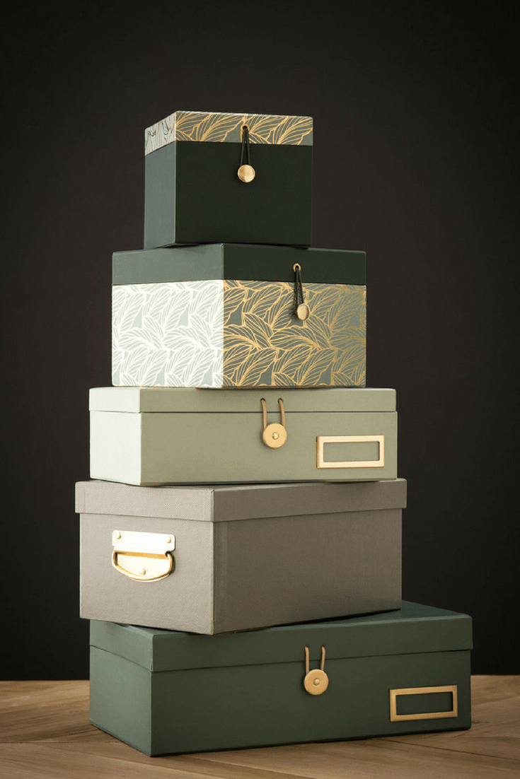 A stack of decorative storage boxes in green colours