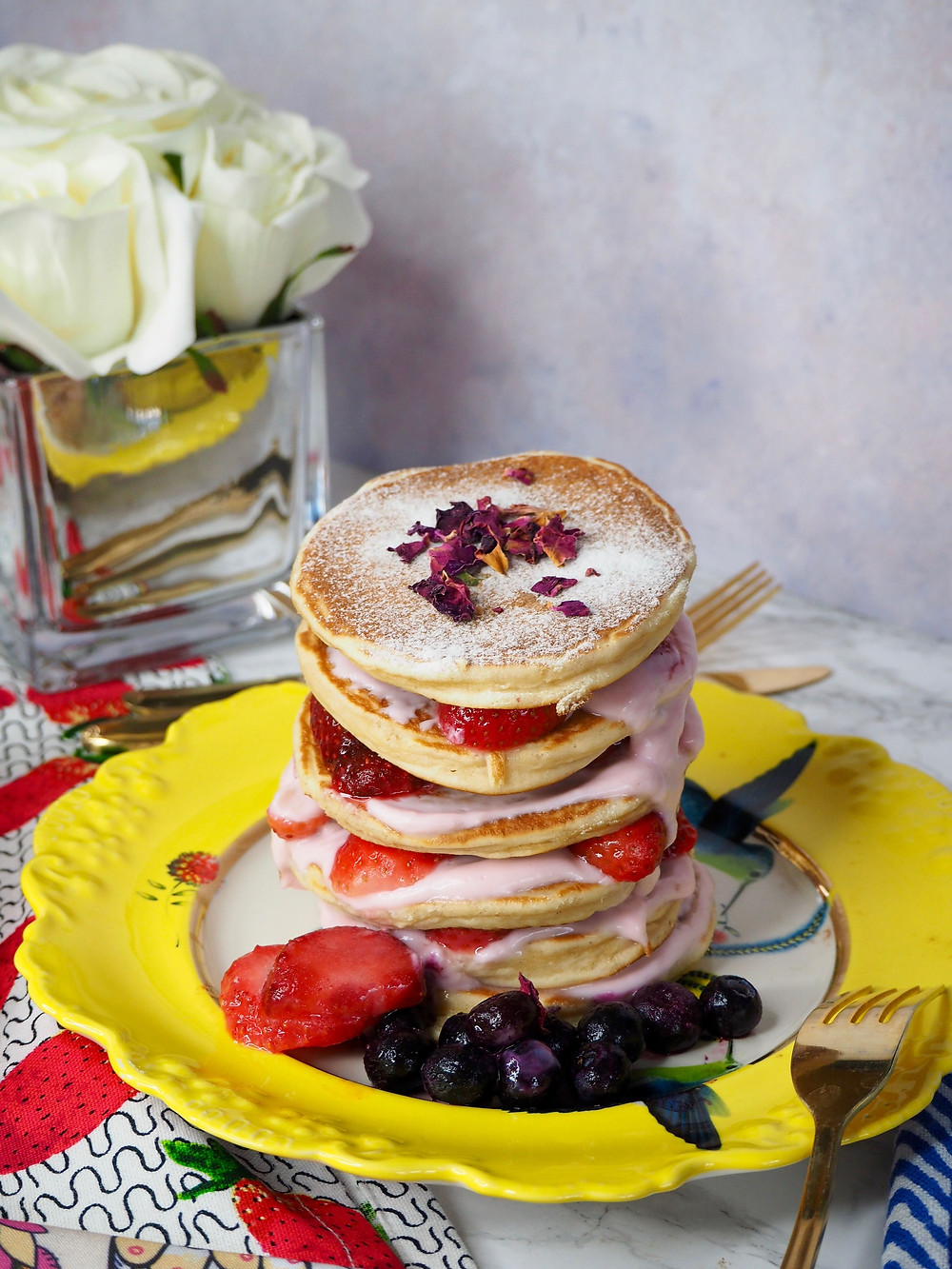 The best pancake recipes ever, stack of pancakes on a yellow plate with strawberries and blueberries and pink yogurt