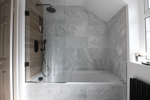 Methven Kaha Concealed Mixer Valve Matt Black, Alsace Honed Marble tiles Mandarin Stone, small bathroom design, renovation ideas, black taps and a black Milano slim Radiator, the Cadmium 18 bath screen The Shower Lab