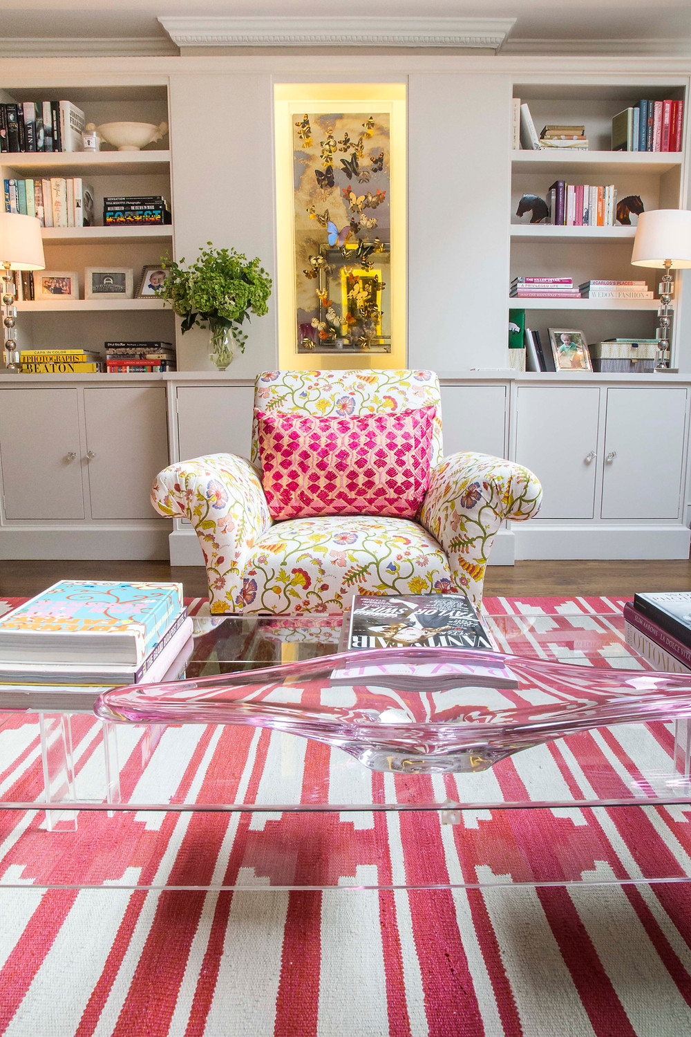 Off white walls in the living room and a perplex coffee table and pink rug floral accent chair Sarah Vanrenen