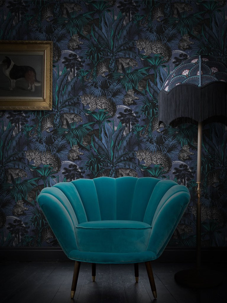 wallpaper divine savages leopards and floral, bold print and teal velvet armchair, floor lamp with long fringe
