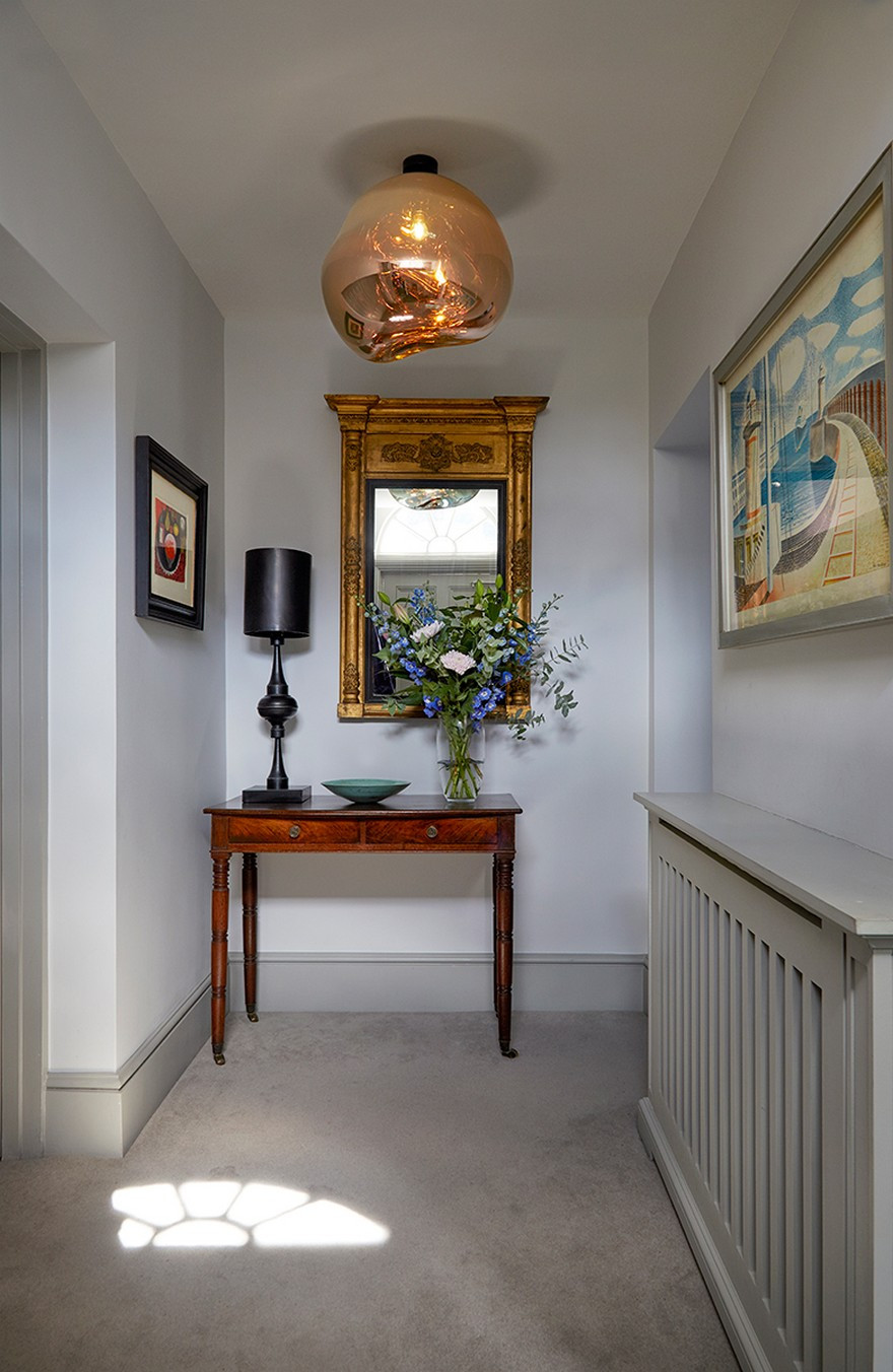 Gilded antique French mirror and tom Dixon pendant light in a grade II listed home