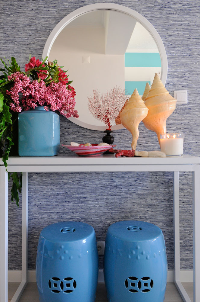 Blue grasscloth wallpaper white round mirror, Palm Beach decor, ceramic stools and flowers in vase, Maria Barros styling