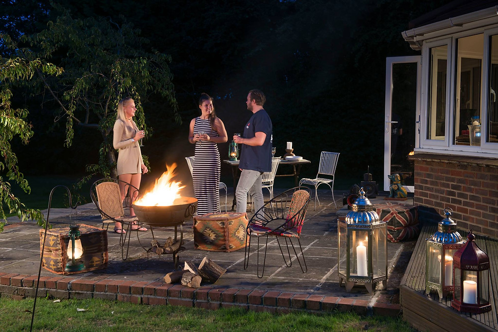 People having a barbeque around an indian fire bowl in their garden, with moroccan outdoors lanterns and indian pouffes