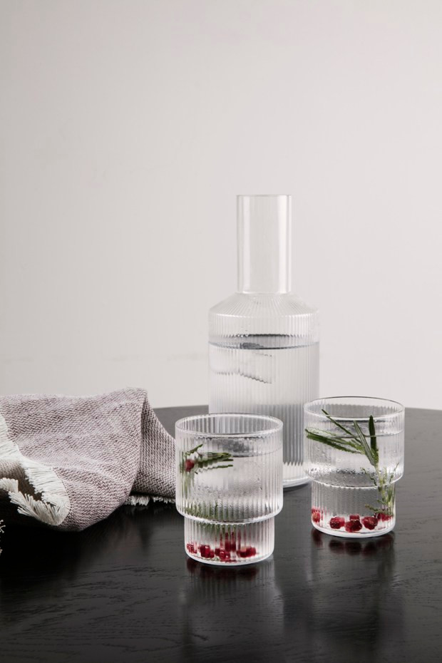 minimalistic jug and glasses with pomegranate seeds and rosemary