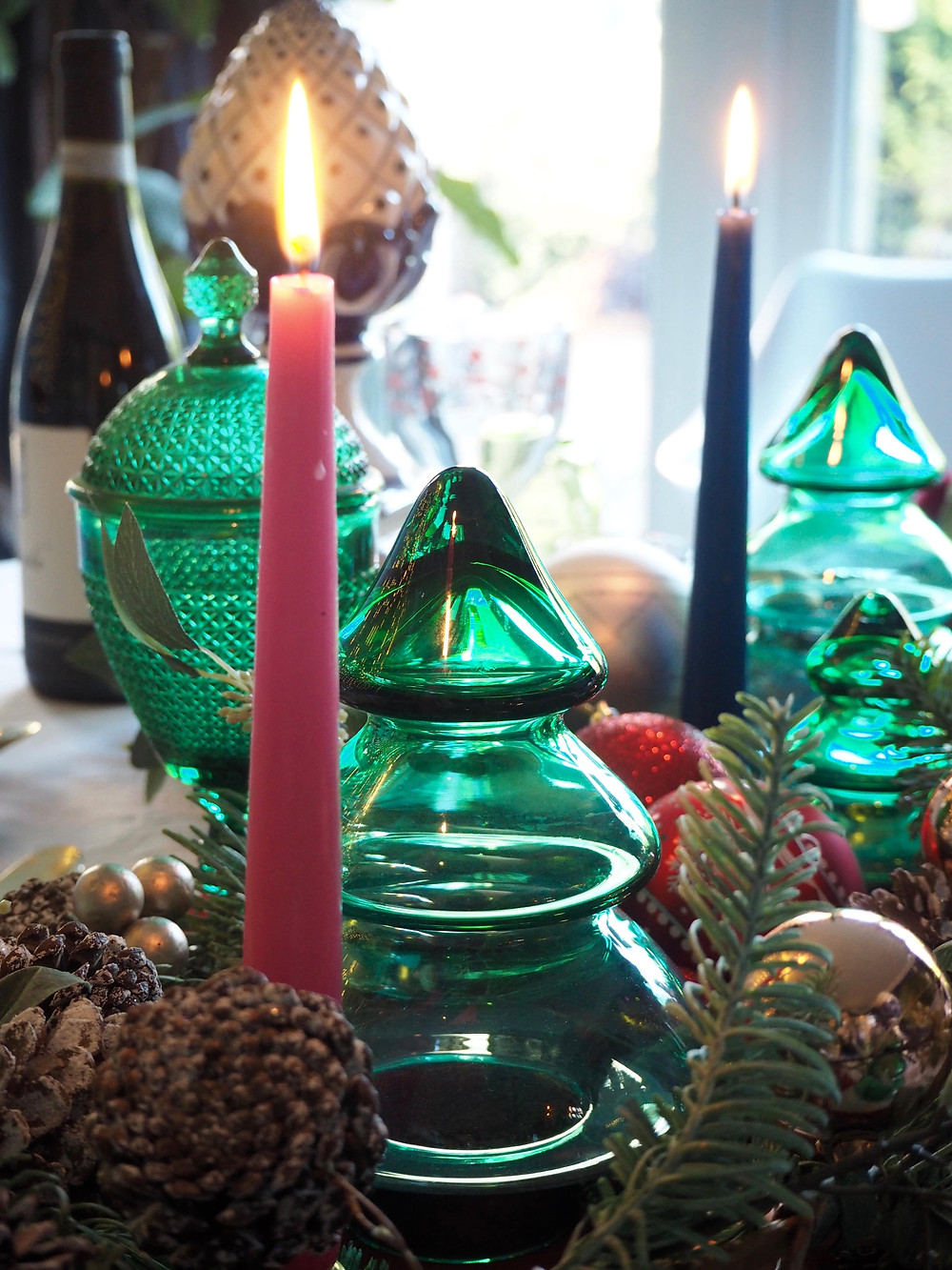 glass tree ornaments in green with candles on a festive Christmas table, centrepiece
