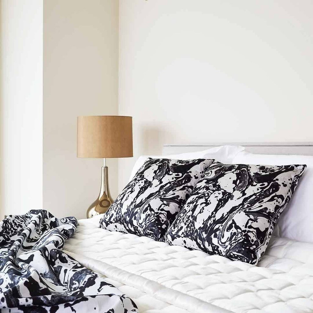 marble effect cushions in black and white on a bed