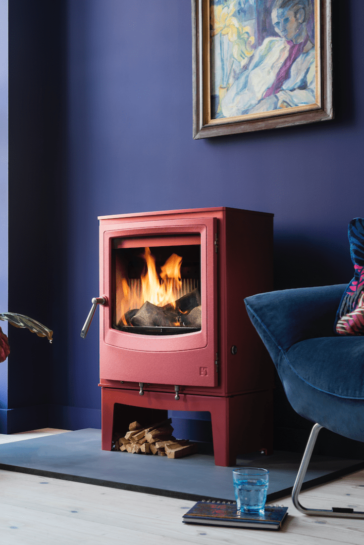 Arada Farringdon wood burning stove in red pink colour in front of a deep purple wall