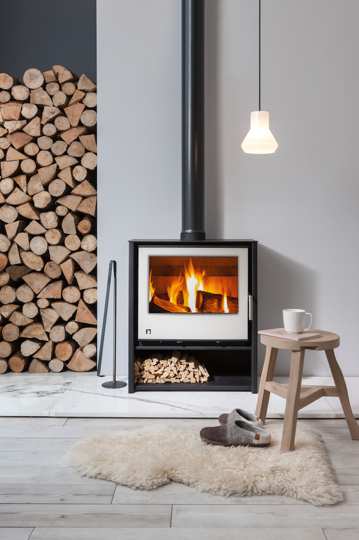 The ARADA i600 Slimline Freestanding wood burning stove and a sheep hide in front of it