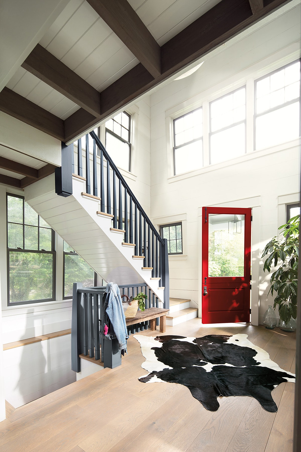 Red door against crisp white board walls and a staircase painted in grey - this is so classy and loving the cowhide rug that modernises the whole look! Benjamin Moore has revealed Caliente AF-290 as its highly anticipated Colour of the Year 2018. Unveiled alongside a corresponding palette consisting of 22 enlivening hues, this vibrant and charismatic shade of red is a bold yet soothing contemporary colour that oozes confidence.