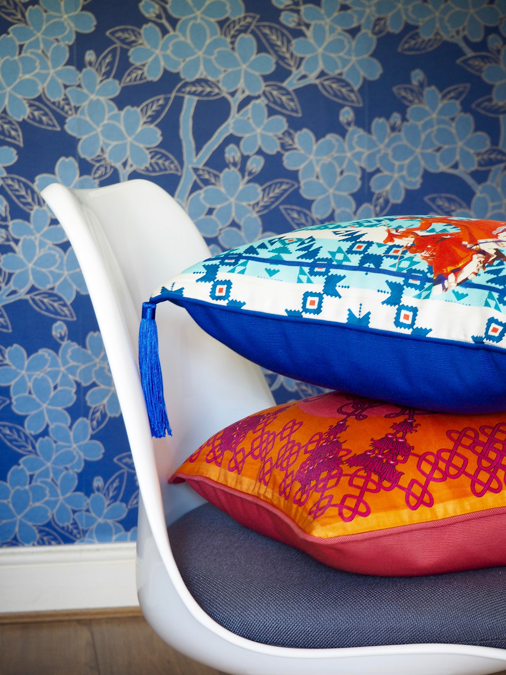 Silk twill blue and pink orange cushions by Bivain on a white Tulip chair against a blue wallpaper background