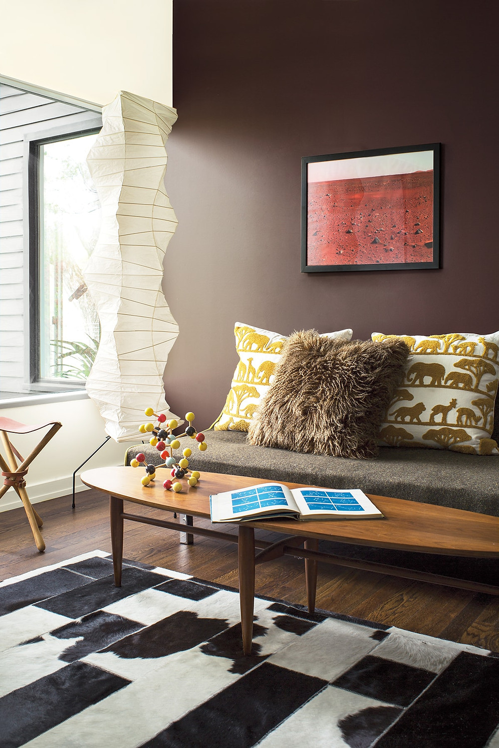 Mid century coffee table and wall art and rice paper lighting fixture, cowhide rug on the floor. Benjamin Moore has revealed Caliente AF-290 as its highly anticipated Colour of the Year 2018. Unveiled alongside a corresponding palette consisting of 22 enlivening hues, this vibrant and charismatic shade of red is a bold yet soothing contemporary colour that oozes confidence.