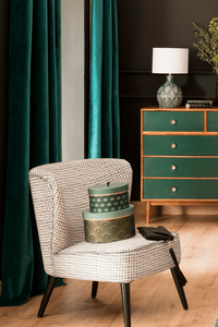 green interior decor inspiration and ideas with cocktail chair and stack of boxes, green velvet curtains