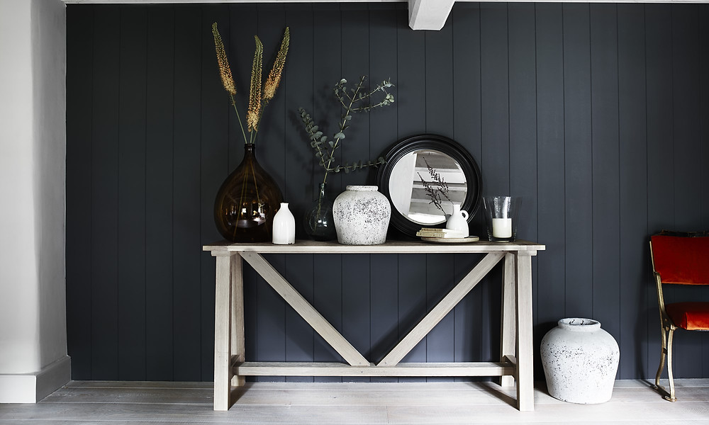 console table in front of dark wall. Round mirror and layered vases