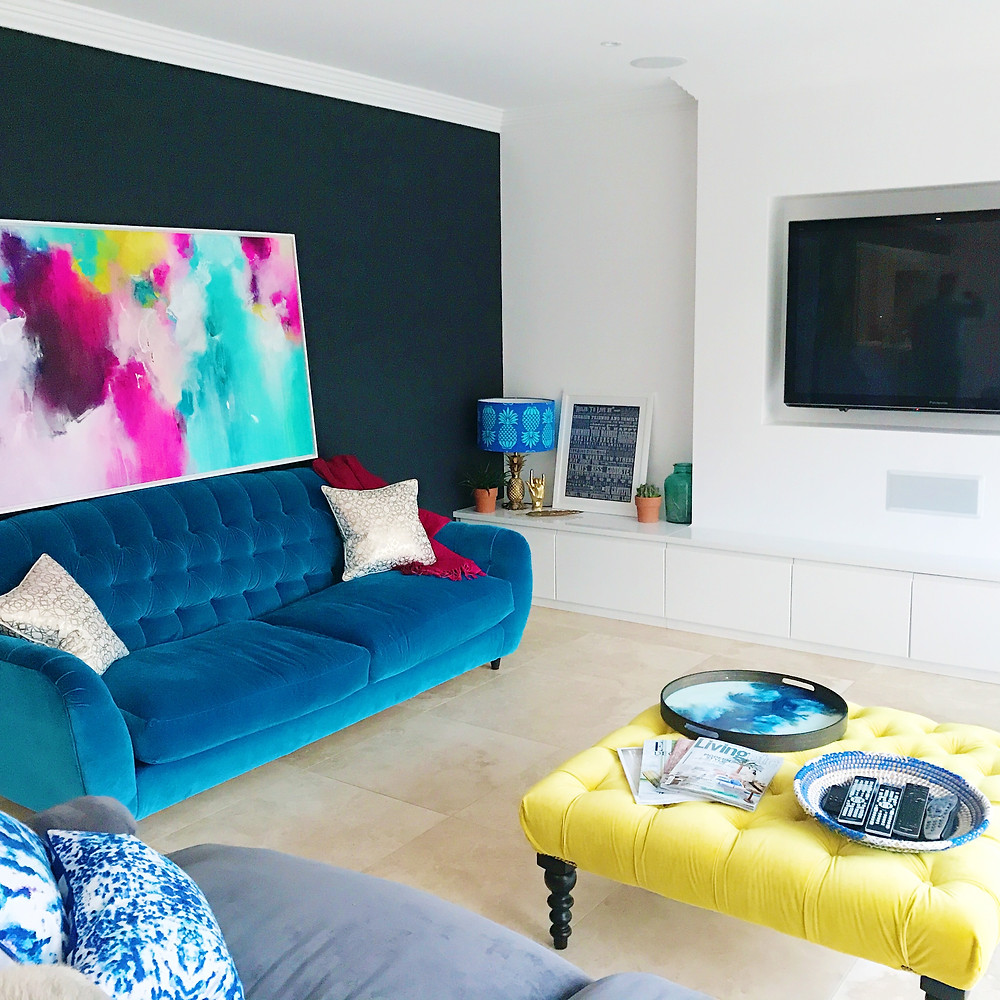 living room with jewel like tones, blue velvet sofa and abstract painting with yellow footstool