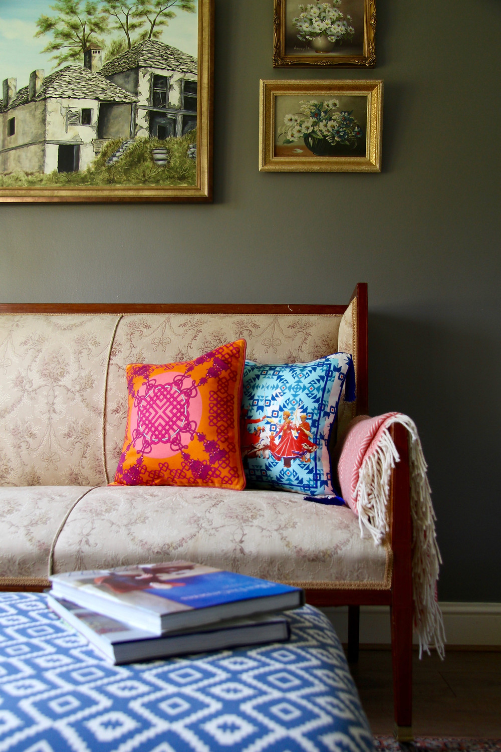 Silk twill blue and pink orange cushions by Bivain on a traditional settee against a grey Farrow and Ball Moles Breath wall with oil paintings and a blue footstool