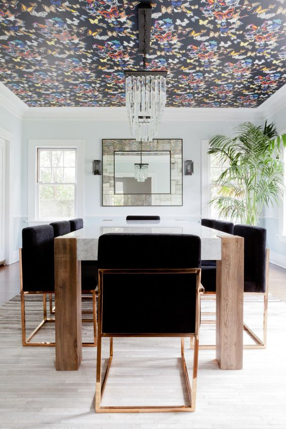 christian lacroix butterflies wallpaper on the ceiling of a dining room, large marble table and black chairs in brass