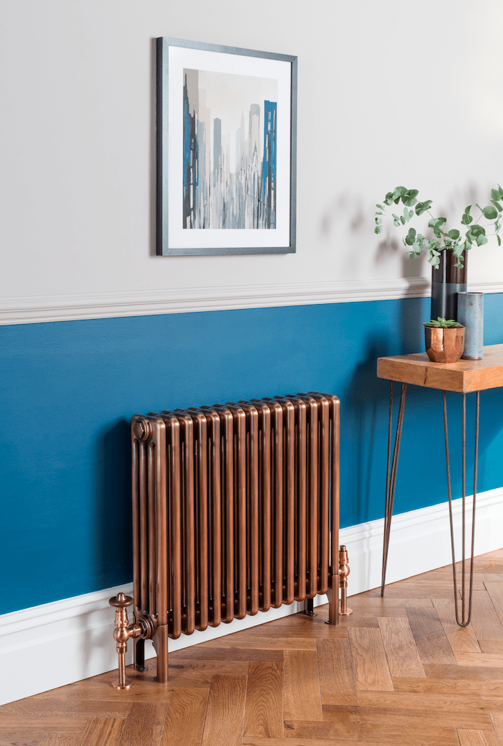 An antique style copper horizontal radiator in front of a blue wall that features art and a chunky wooden top console table with bronze legs.