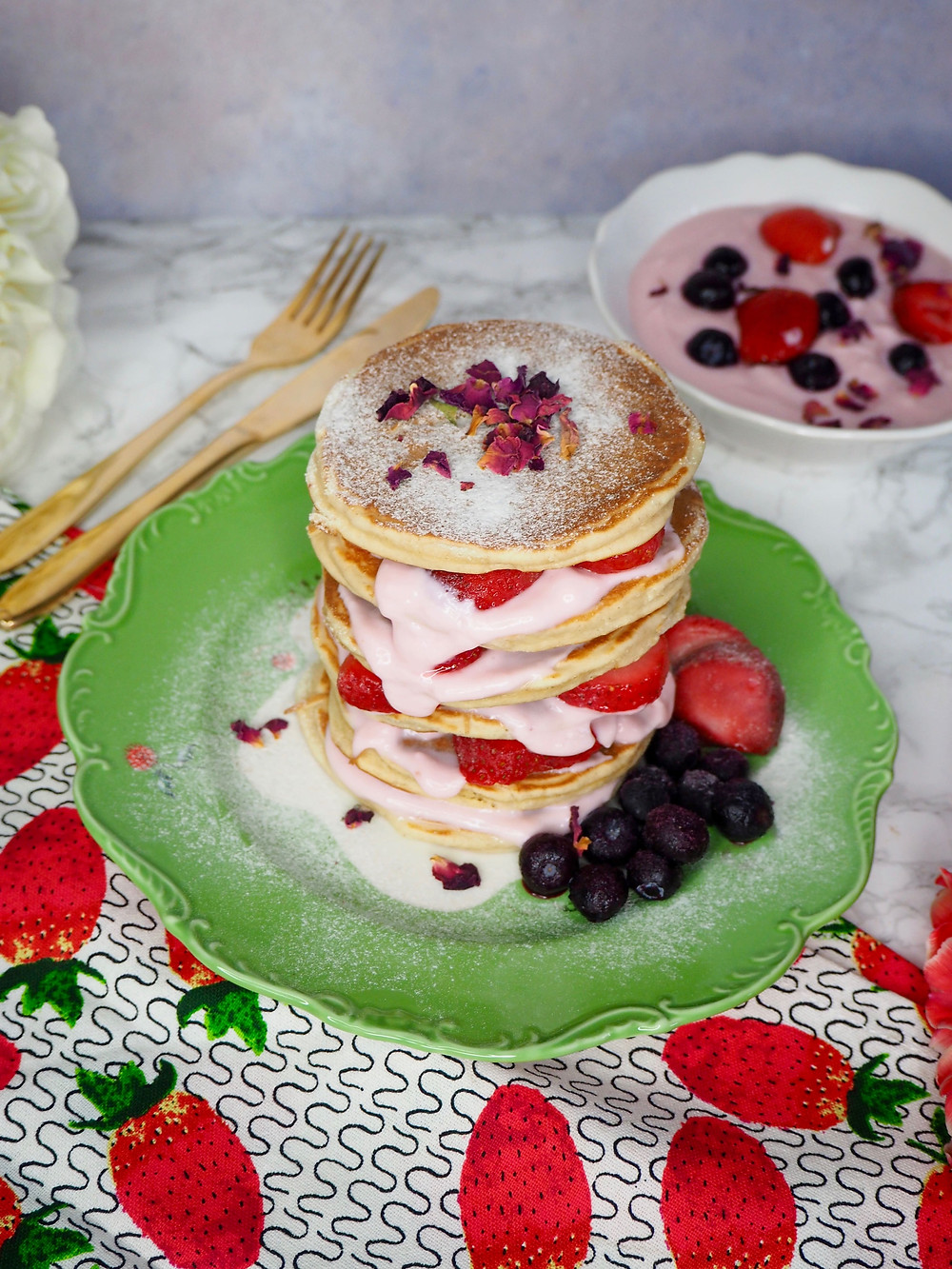Buttermilk pancakes on a green Anthopologie plate, servied with pink strawberry yogurt and real strawberries and blueberries dusted with sugar