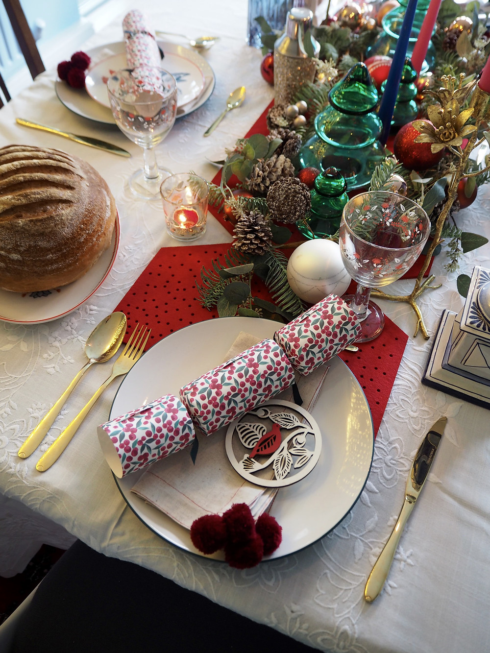 How to set your Christmas table with John Lewis Christmas crackers in pink and green with blue background and fairy lights, felt cracker centrepiece from the Folklore collection. Gold cutlery table setting. white vintage tablecloth