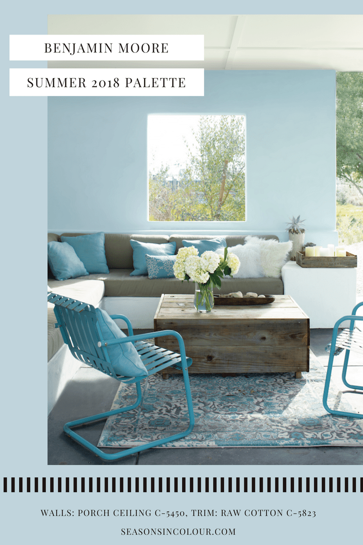 Benjamin Moore wall painted in Porch Ceiling which is a light blue colour. Applied here in a living room with repurposed coffee table and blue metal chairs, blue cushions and cream hydrangeas in a vase, views of the countryside. Modern living ideas