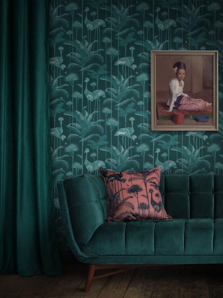 Bold print wallpaper in green behind a green velvet sofa and green velvet curtains. Bold statement print