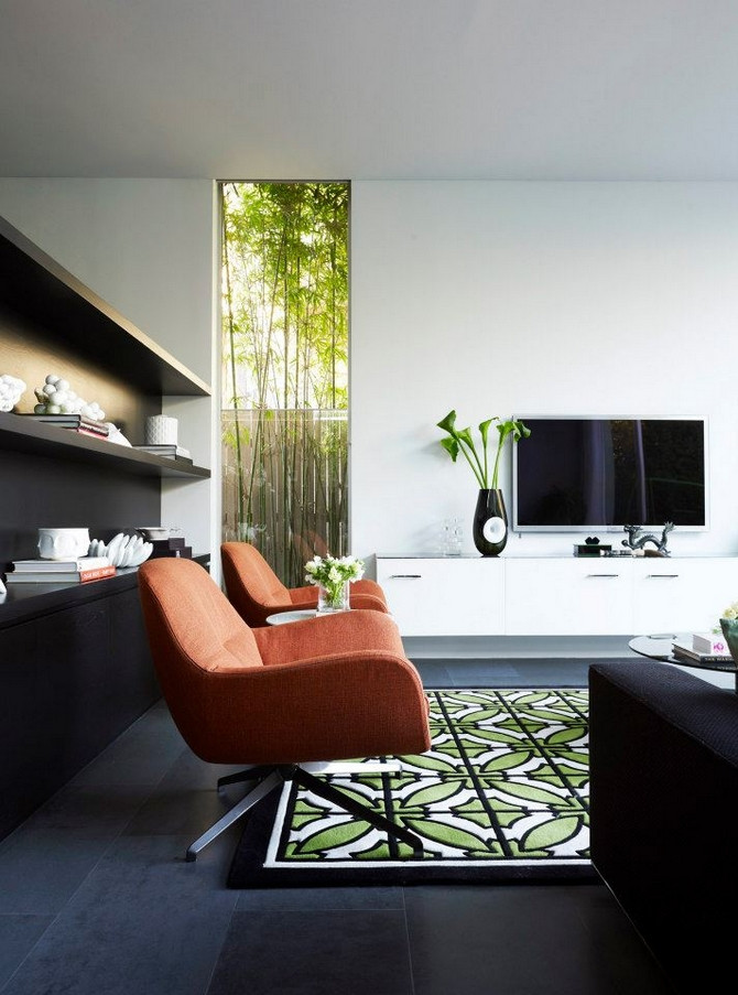 Mid century modern interiors Five Dock House by Greg Natale black build in bookcase and swivel chair green rug