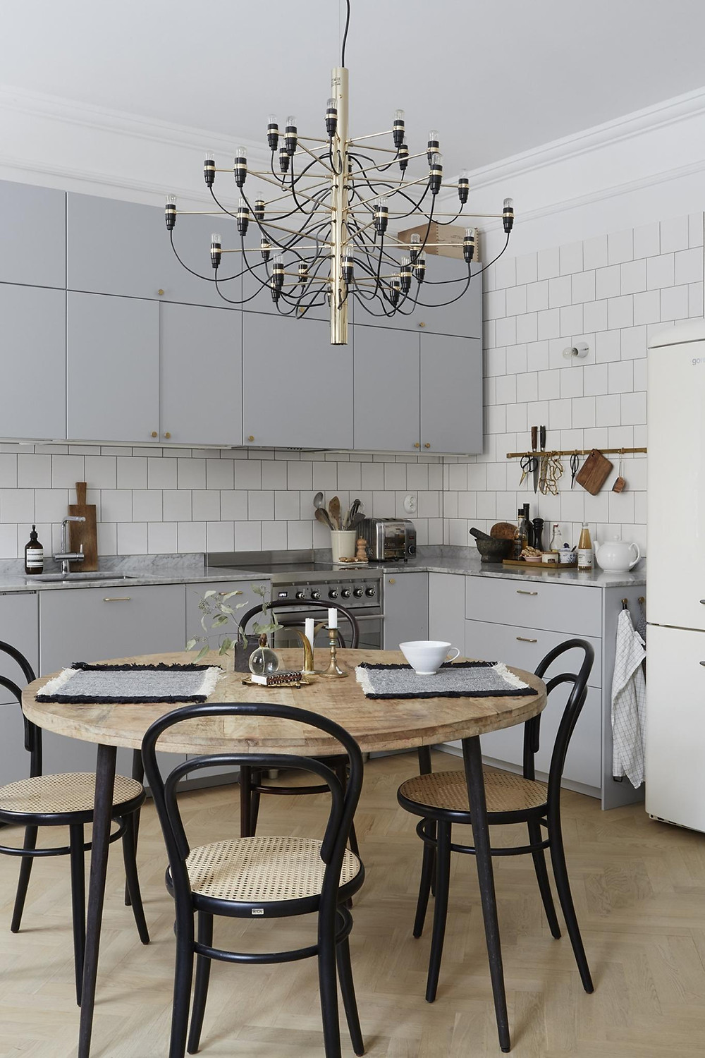 Scandinavian interior design kitchen decor with square tiles and retro fridge, off grey cabinets with brass handles and bistro chairs