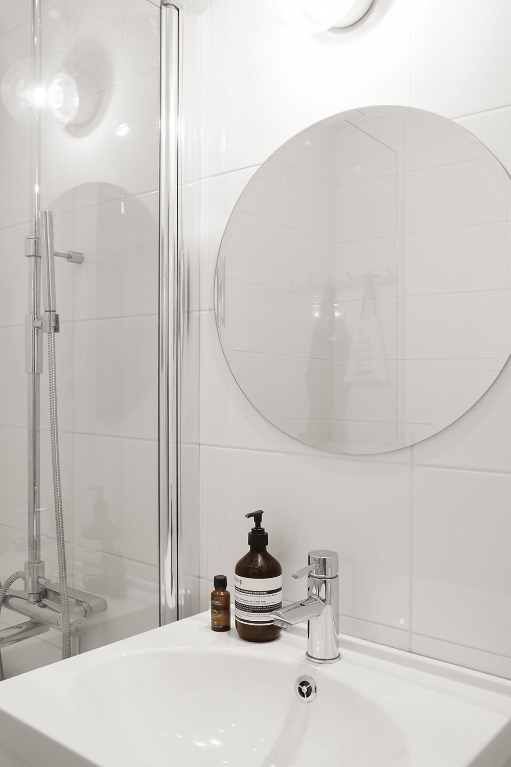 Scandinavian interior design bathroom with white tiles and round mirro
