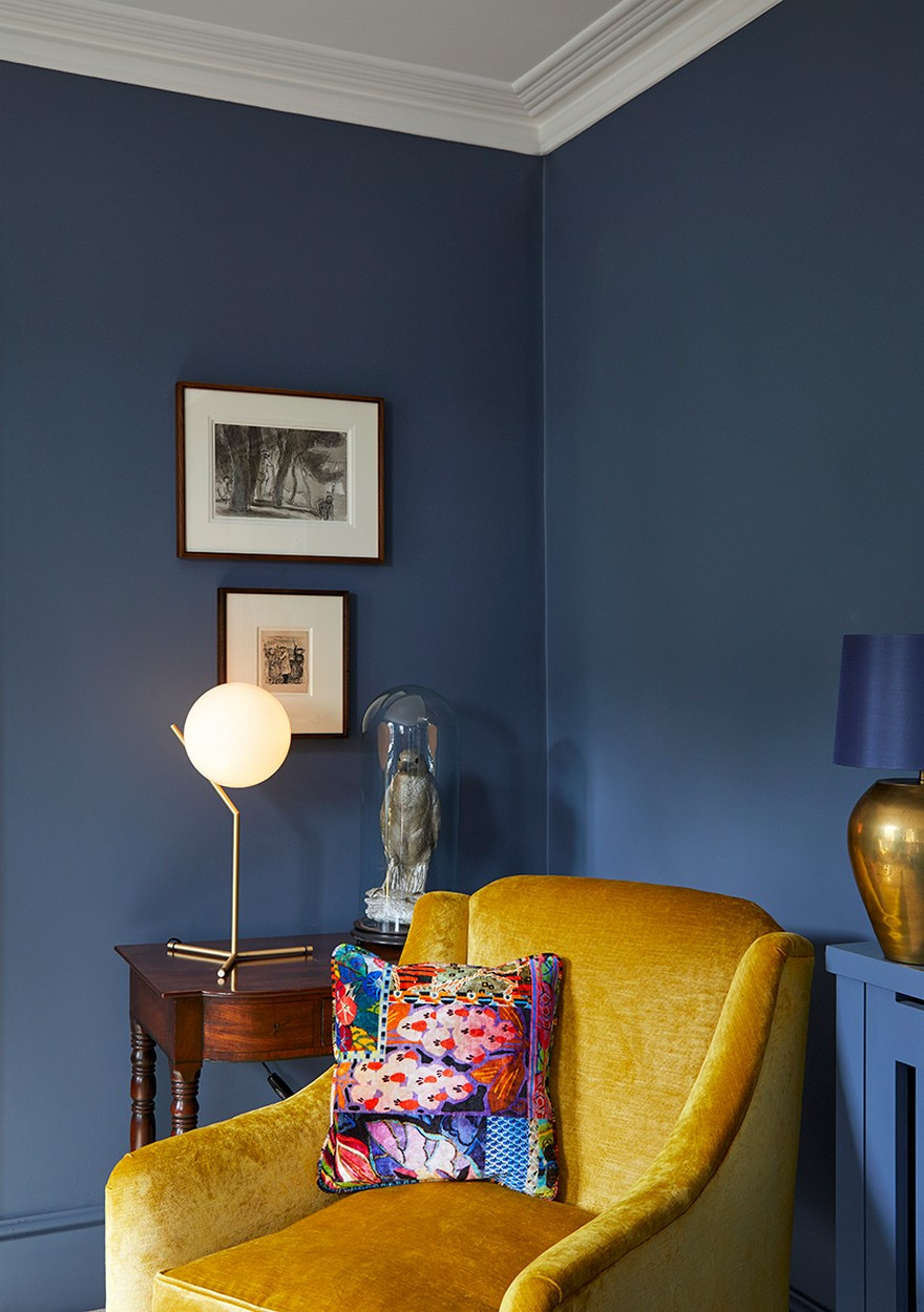 Yellow accent chair in front of blue walls and a FLOS table lamp in front of etchings