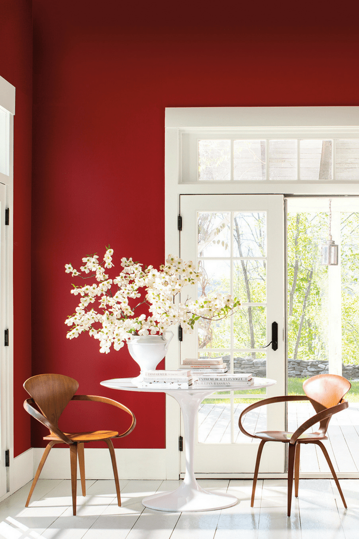Red dining room decor with mid century tulip table and wooden chairs. Double french doors leading to a garden. Benjamin Moore has revealed Caliente AF-290 as its highly anticipated Colour of the Year 2018. Unveiled alongside a corresponding palette consisting of 22 enlivening hues, this vibrant and charismatic shade of red is a bold yet soothing contemporary colour that oozes confidence. Wall colour - Caliente AF-290, Trim & Door colour - White Opulence OC-69
