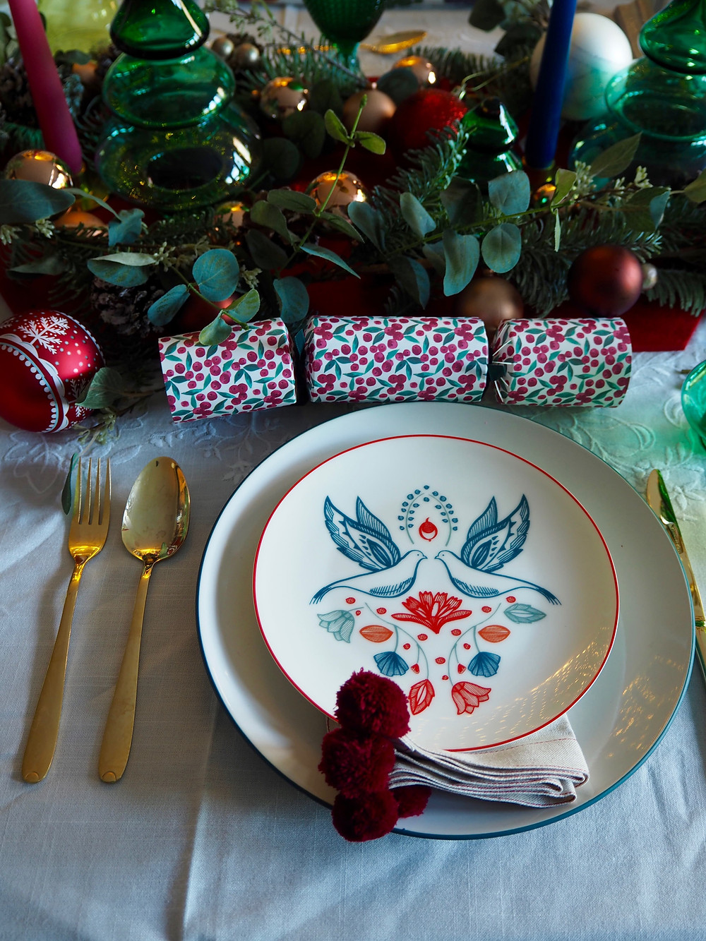 How to set your Christmas table with John Lewis Christmas crackers in pink and green with blue background and fairy lights, felt cracker centrepiece from the Folklore collection. Gold cutlery table setting. Plate with doves in blue and red.