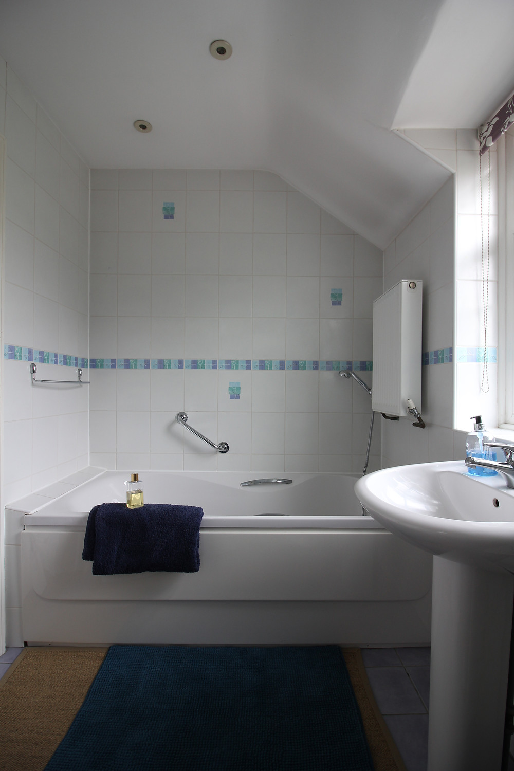seasonsincolour bathroom makeover, a bathroom with square white tiles and blue border, chrome towel rail and a single ended bathtub.