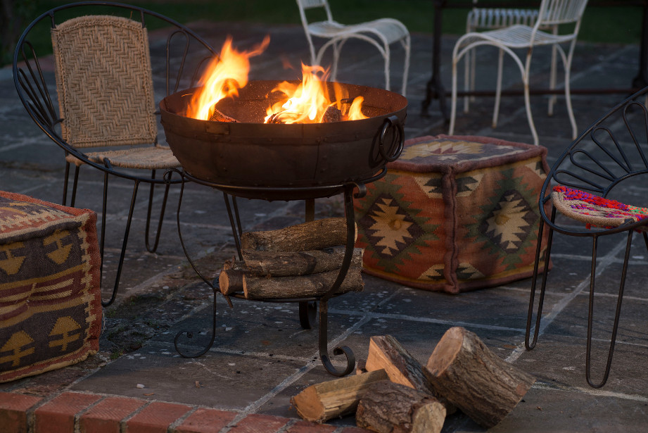People having a barbeque around an indian fire bowl in their garden, with moroccan outdoors lanterns and indian pouffes, chindi chair