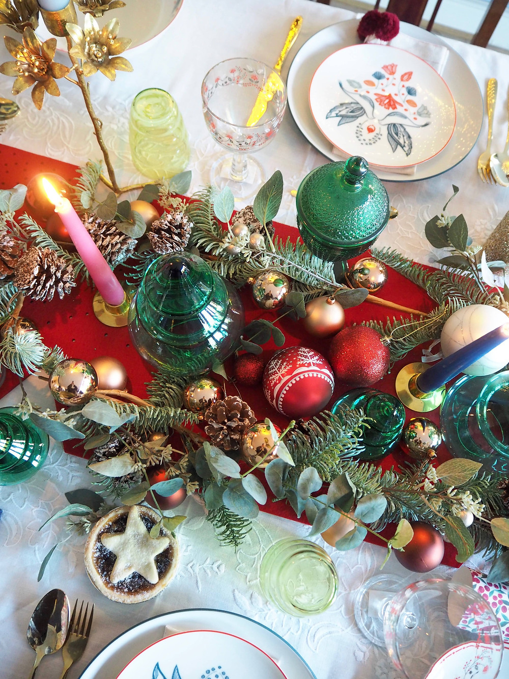 How to set your Christmas table with John Lewis Christmas crackers in pink and green with blue background and fairy lights, felt cracker centrepiece from the Folklore collection. Gold cutlery table setting. white vintage tablecloth . Pink candles.