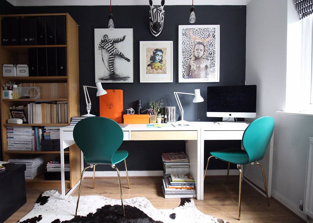 Kitsch dining chairs racing green with brass legs in an eclectic home office against Farrow and Ball Railings with Anglepoise white lamps and IKEA desk